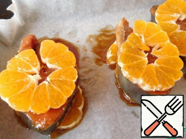 On top of the fish, put another layer of tangerines. Put in the oven, preheated to 200*, for 15 minutes.
