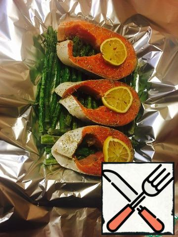 Season with salt and pepper, sprinkle with rosemary, cut three slices from half a lemon and put on the fish, and squeeze the juice from the rest of the lemon on the fish.