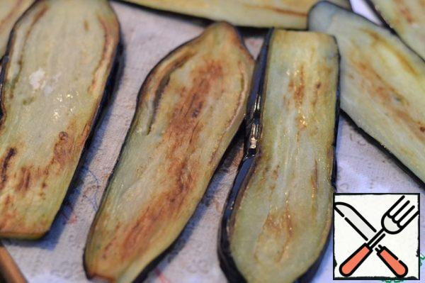 Wash the eggplant and dry it with kitchen napkins. Fry in sunflower oil until brown. Spread the fried eggplant on a napkin to drain the excess fat.