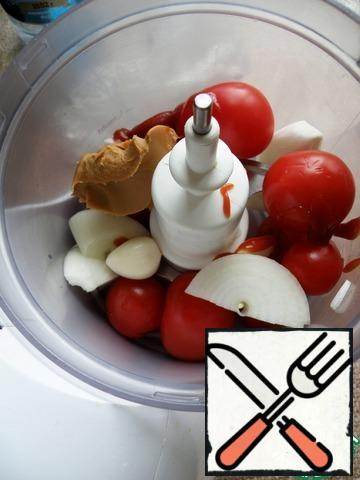 In a blender, beat the onion, garlic, tomatoes and ketchup with peanut paste into a smooth mass.
