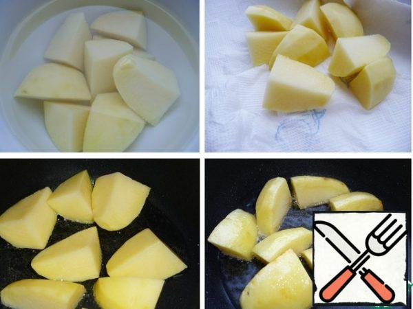 Peel the potatoes, cut them into large pieces, wash them with cold water, and leave them in the water for 10 minutes. Dry with a paper towel and fry in a frying pan in preheated vegetable oil until light brown. Place on a plate.