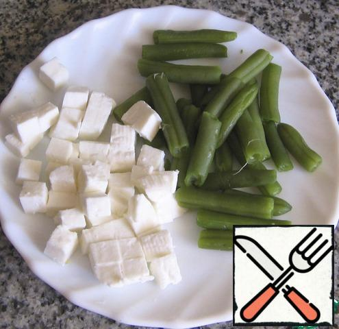 Wash, peel and slice the string beans. Boil it in salted water for 10 minutes. Cut fresh cheese into cubes.