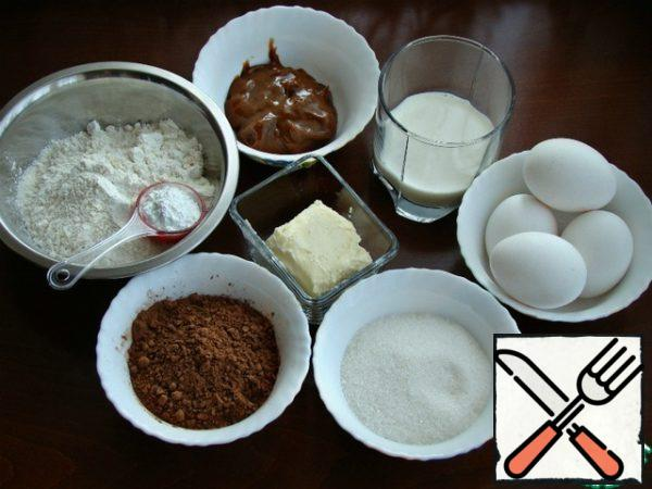 Prepare all the necessary ingredients for a chocolate-caramel sponge cake.