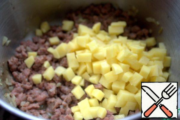 Add diced potatoes to the fried minced meat.