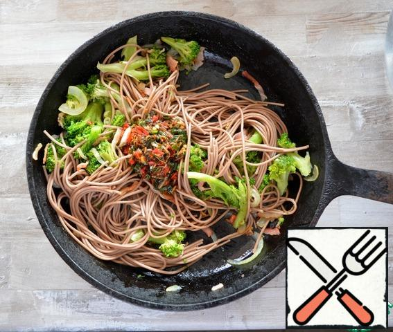 Boil buckwheat soba noodles in boiling water without salt for 5 minutes, flip them on a sieve and add them to the contents of the pan. Pour in the dressing, mix and remove from the heat.