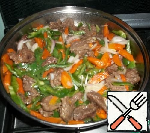 Ginger, garlic, hot pepper, pound in a mortar, finely chop the herbs. When the meat juice is almost evaporated, add the carrots and 2 tablespoons of oil. Fry until the carrots are half cooked, under the lid, sometimes stirring, Add pepper and onion.