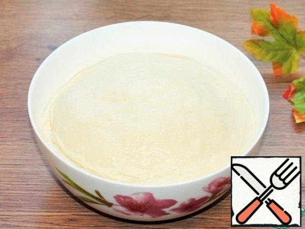 Grease the dough and bowl with vegetable oil (0.5 tbsp) and cover tightly with a lid or film. Put the bowl in a warm place to lift the dough 2.5 times, for 60 minutes.