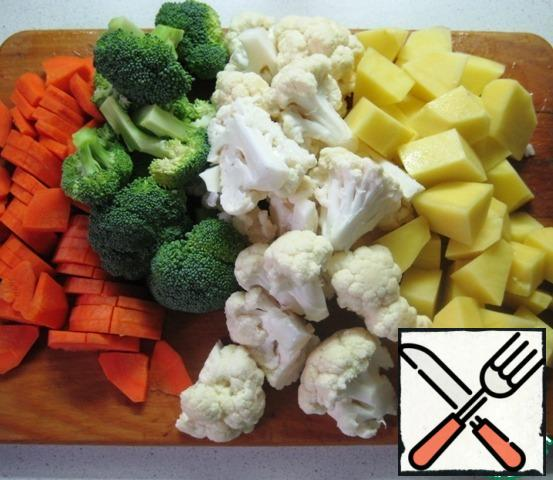 Carrots and potatoes cut into pieces of approximately the same size, disassemble the broccoli and cauliflower inflorescences.