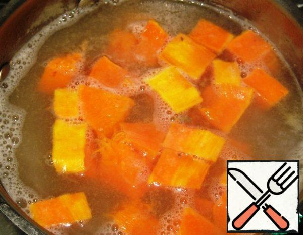 When the broth with potatoes boils, reduce the heat under the saucepan, cook for 4-5 minutes. Then add the pumpkin slices.