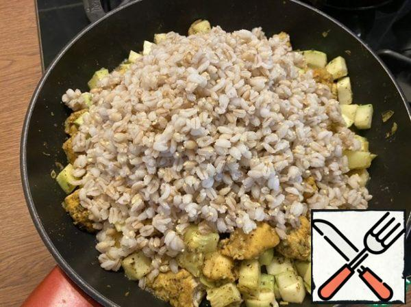 Then add sunflower oil. After adding the oil, pour the cooked pearl barley into the pan, mix well and close the lid. Simmer for 2 minutes.