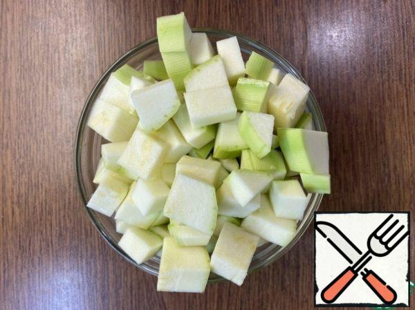 While the chicken fillet is cooking, cut the peeled zucchini into medium cubes.