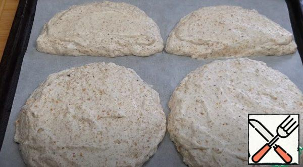 On parchment paper, draw a template (2 circles and 2 semicircles with a diameter of 18 cm) and lay out the dough, visually dividing it into three parts (300 grams each). Bake the cakes for 35 minutes, and then leave to cool completely.
