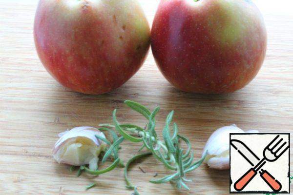 Cut the apples, remove the seed pods and cut each into 6 parts. Crush the garlic. Clear the rosemary needles.
