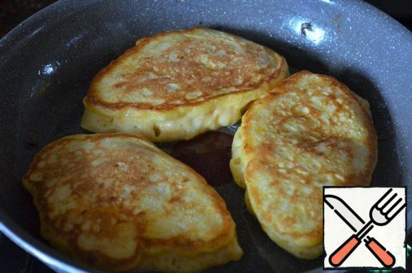 Turn it over with a spatula, cover with a lid, and fry for another 2 minutes, the heat is lower than average. Hot spread on a platter. For frying, re-pour and heat the oil, so fry all the pancakes.