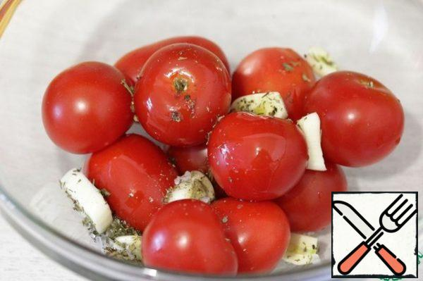 Put the cherry and garlic in a bowl, add the herbs of Provence, salt, pepper and drizzle with oil.