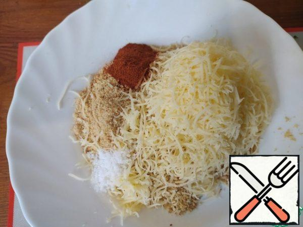 Grate the cheese on a coarse grater. Mix with breadcrumbs. Add sweet paprika, salt and mix well.