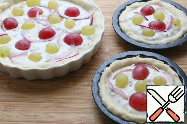Spread the filling on the dough, on top of the onion, cut into thin half rings, put the grapes, sprinkle with nuts and, if desired, pink pepper.