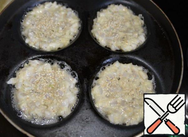 """Pour the oil into a hot pan. I use a frying pan for frying pancakes. Put a full spoonful of squid """"dough"""" on a hot frying pan with oil, lightly sprinkle sesame seeds on top. Fry on medium heat for 3 minutes."""