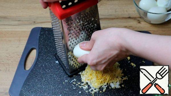 Boil, cool and peel the eggs. Grate them on a fine grater.