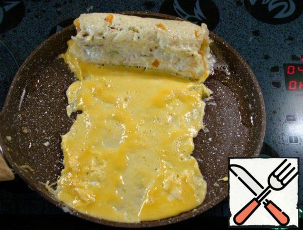 Then move the roll to the edge and carefully pour 1/4 of the egg omelet, trying to form the edges and width of the omelet, the width of the rice roll. Add vegetable oil if necessary.