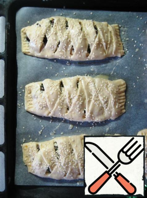 Put the formed pies on a baking sheet and let rest for 10-15 minutes. Then brush with beaten egg and sprinkle with sesame seeds.