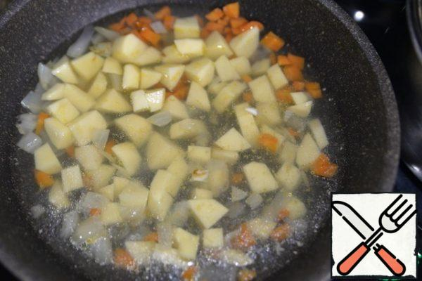 We take a frying pan with high sides or a saucepan, heat it, pour oil. Fry the vegetables until soft over medium heat, put the diced potatoes, fill with fish broth.