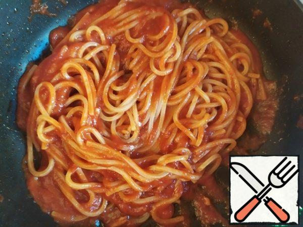 When the spaghetti is ready, put the Cup of water away from them. Drain the rest. Transfer the spaghetti to the sauce and mix well. If the sauce is too thick, add a little water and stir.
