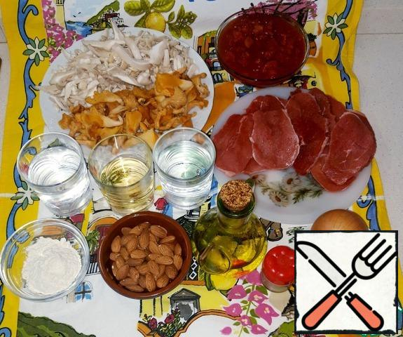 First, we will prepare the necessary products. Cut the veal fillet into 1 cm thick plates. Dried mushrooms should be pre-soaked for 20-25 minutes in warm water,and canned throw in a colander to leave the liquid. Fresh ones can be immediately cleaned and randomly sliced. Tomatoes cut into small slices or three on a large grater. I have 1 can of tomato slices in their own juice.