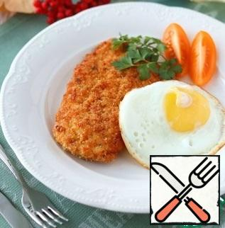Serve schnitzel traditionally with fried eggs and fresh vegetables. Bon Appetit!