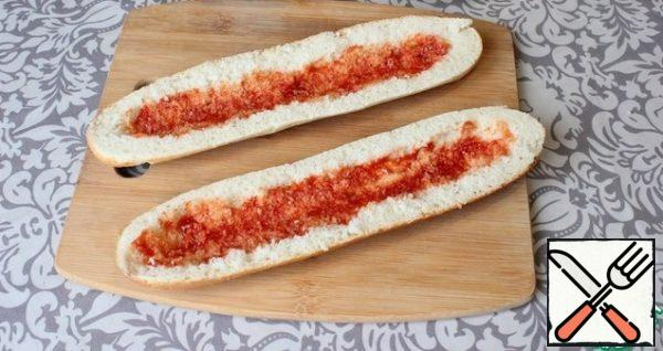 I cut the baguette lengthwise into two parts. Removing the crumb. I smear the inside of the baguette with ketchup.