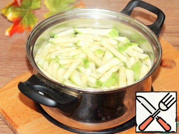 Cut the zucchini into strips and blanch in boiling water until half cooked. Then drain the water and dry the squash a little in a sieve.