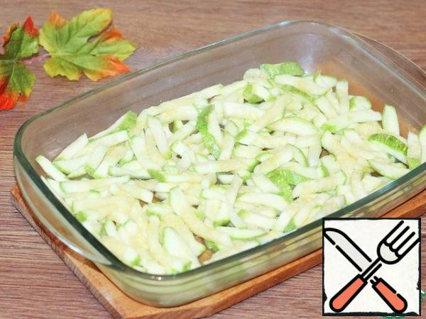 Grease the baking dish with sunflower oil and lay out the zucchini.