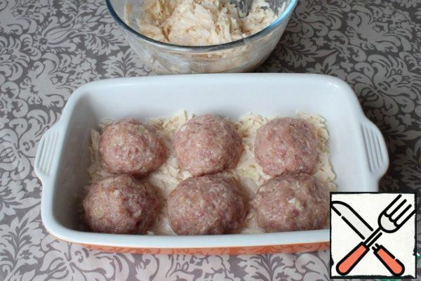 I lubricate the baking dish with sunflower oil. I put half of the grated potatoes on the bottom. I spread the balls of cutlets on top.