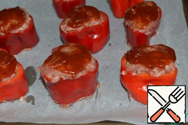 Stuff the pepper rings and place them on a baking sheet covered with parchment. Mix the ketchup and brown sugar and brush the surface of the peppers. Send to a preheated 180*C oven. Bake for 35 minutes, then sprinkle with grated cheese and bake for another 5-8 minutes.