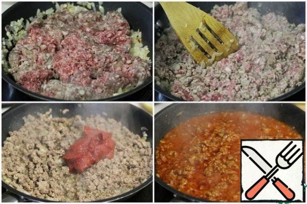 Put the minced meat in the pan, fry it, breaking the lumps with a spatula. Add the tomato paste and fry, stirring. Then pour in 200 ml of water, stir, bring to a boil and remove from heat.