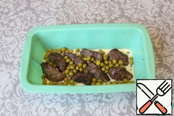I will bake in a silicone rectangular shape (21 by 11 cm). The sides of the form are slightly greased with vegetable oil (just in case). At the bottom, pour 5-6 spoons of filling. I spread out half the pieces of liver. Sprinkle with half of the green peas.