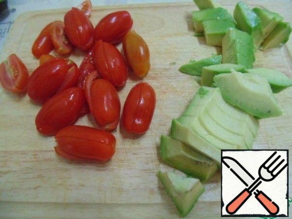 Cherry tomatoes cut into halves, avocado cubes.