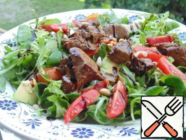 Collect the salad: put lettuce leaves, tomatoes, avocado, liver on plates, pour the dressing, sprinkle with pine nuts, decorate with balsamic cream.