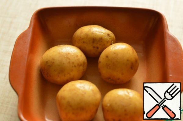 Wash the potatoes and bake in the oven until soft.