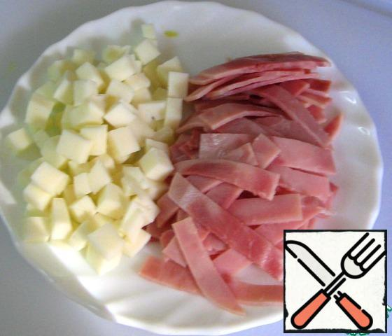 Cut the ham into thin and short strips. Cut the cheese into cubes.