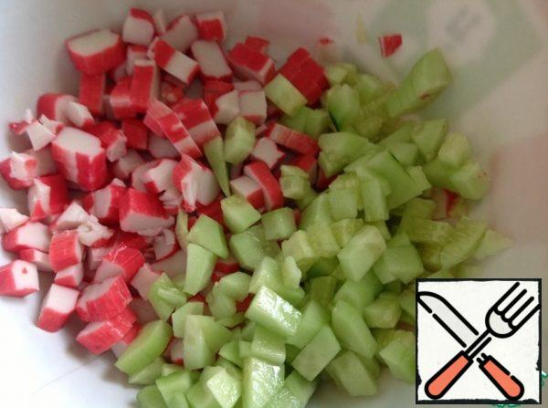 Cut the crab sticks into cubes, peel the cucumbers and cut them in the same way as the sticks.