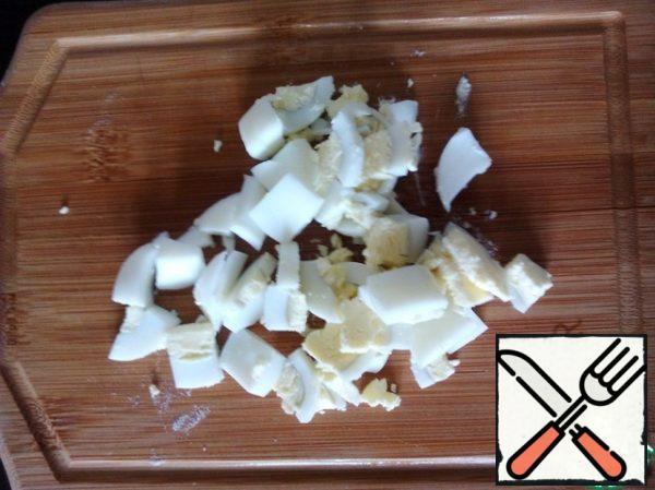 Boil the eggs, cut into large cubes.