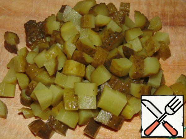 Cut the pickled cucumbers into cubes.