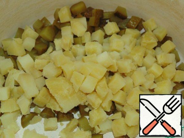Cut the pickled cucumbers into cubes. Peel the cooled potatoes and cut them into cubes.