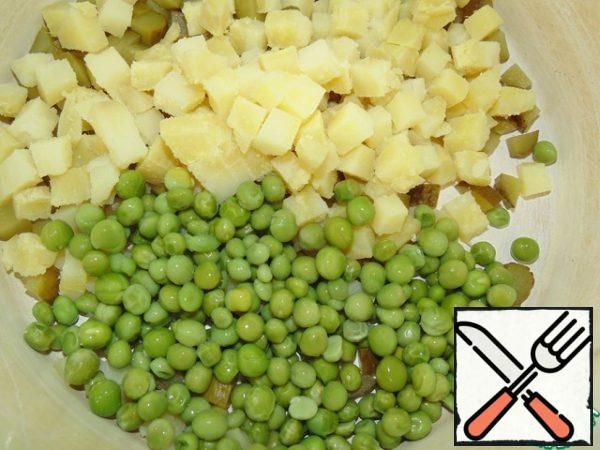 Add the cooled peas to the potatoes with cucumbers.