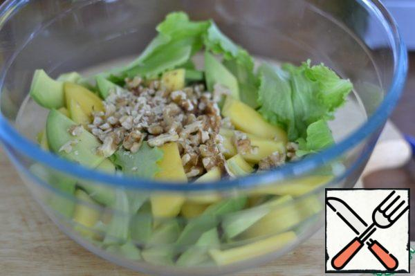 In a bowl place the arugula or salad Insalatina me, to me it is more like it. Cut the nuts into small pieces Add avocado and mango to the salad. Season with salt and pepper.
