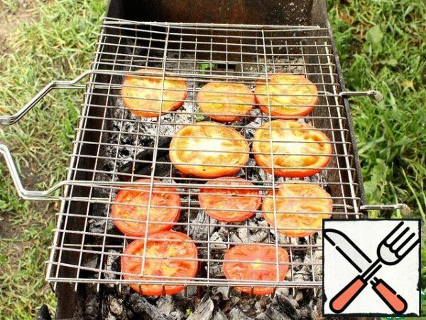 Tomatoes wash, dry and cut into circles. Put on the grill and fry on the grill until ready. Baked vegetables, after removing from the grill, immediately cut into random pieces and put in a Cup.