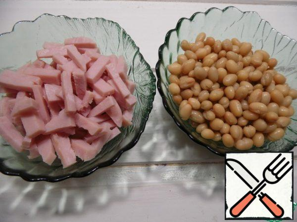 drain the liquid from the beans, cut the ham into cubes.