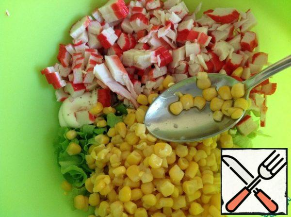 Pour in the corn. Cut the crab sticks into cubes. Mix the salad.