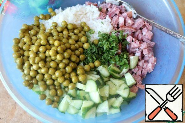 In a deep bowl, combine the washed rice, diced sausage, cucumber, herbs and peas.